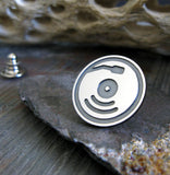 Silver and Black record pin on gray rock with driftwood