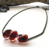 red glass beads on oxidized sterling silver chain white background with driftwood