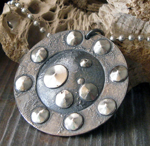 gunmetal and silver dot pendant necklace on gray stone with driftwood