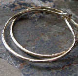 Hammered gold hoop earrings on gray rock