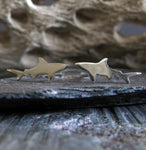 sterling silver shark earrings on gray stone with driftwood