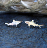 Silver Shark stud earrings on dark blue background with driftwood