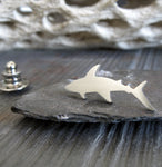 Silver shark tie tack pin sitting on gray rock with driftwood