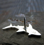 back side of silver shark lapel pin on gray rock