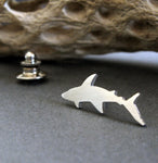 Silver tie tack shark pin shown on a dark background with driftwood