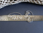 Sterling Silver Triskele Spiral wirewok earrings on ruler for measurement