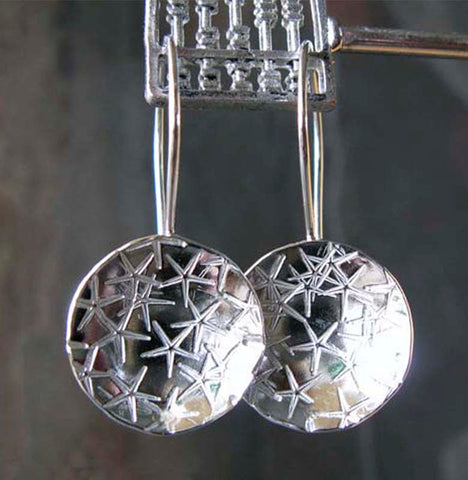 Silver circle starfish disc earrings hanging gray background
