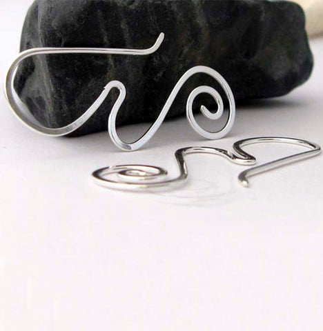 Silver wave and spiral earrings on white background with black rock