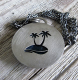 Palm Trees cut out on back of sterling silver pendant on wood grain