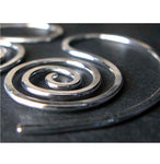 Close up of silver spiral earring on black background