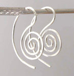 hanging silver spiral earrings on gray background