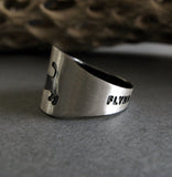 Side View of Sterling Silver Ring With dog tail on dark gray with tree branch
