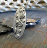 Oval silver ring with dots and wavy line on rock with driftwood