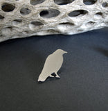 Silver Raven lapel pin sitting on black background with dirftwood