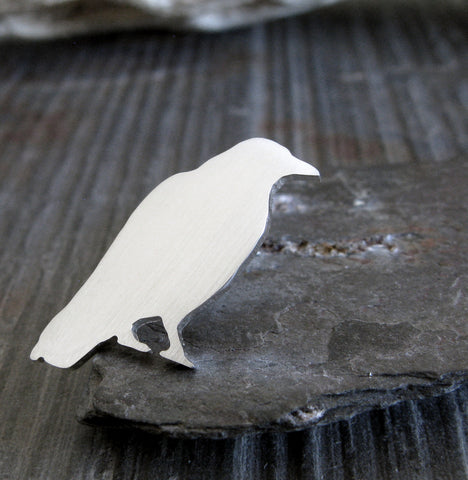 Silver Raven lapel pin sitting on gray stone