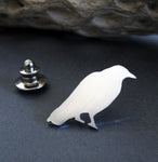 Silver Raven lapel pin sitting on black background with driftwood