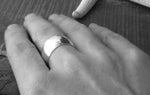 Wide sterling silver ring band shown on hand in black and white