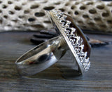 Side view of sterling silver gemstone ring on gray with tree branch
