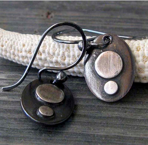 silver and black oval earrings on gray stone with white starfish