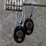 silver dot oval earrings hanging from abacus in front of gray stone