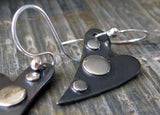 Gunmetal heart earrings with silver dots on gray stone tile