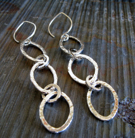 silver oval dangle earrings on gray stone