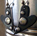 black heart with silver dot earrings in front of tin can