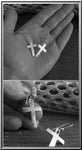 silver cross earrings held in hand