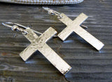 silver cross dangle earrings laying on gray stone