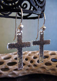 hanging silver cross earrings with driftwood and light blue background