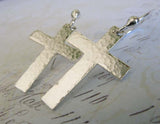 silver cross dangle earrings on pastel background