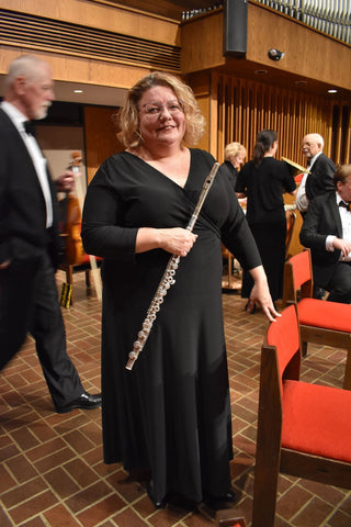 kate in a black maxi dress holding a flute