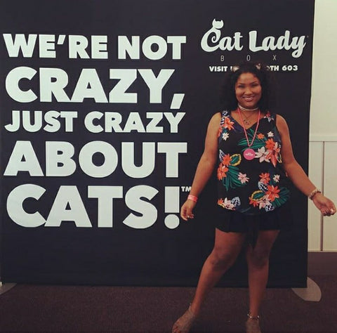allegra standing next to a sign that says we're not crazy, just crazy about cats