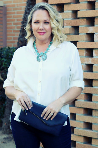 Danielle in a white blouse holding a large navy clutch purse