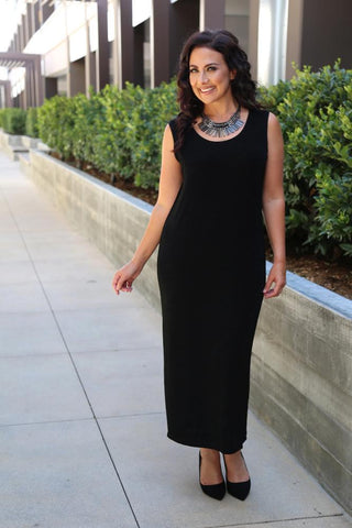 a smiling dark haired woman wearing a black maxi tank dress