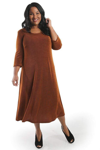 a dark haired women with brown skin wearing a rust colors a line maxi dress