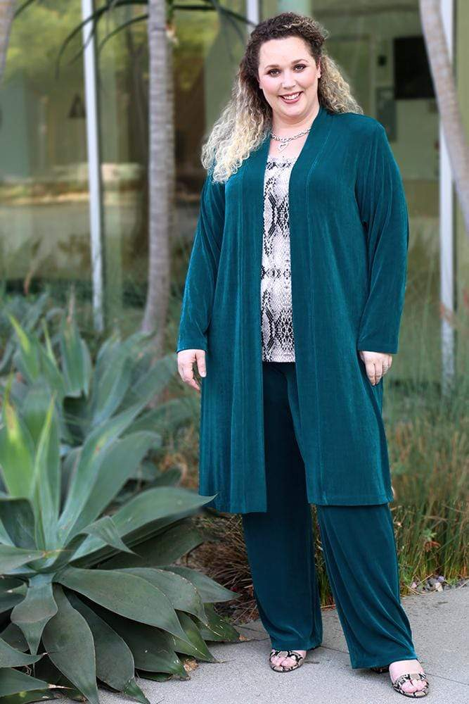 a smiling woman wearing deep teal pants, a deep teal duster, and a python print shell