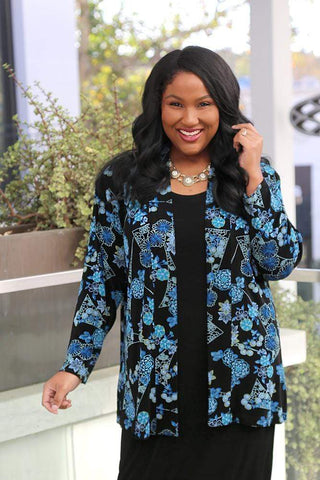 a smiling dark skinned, dark haired woman in a blue print jacket