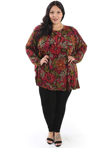 a dark haired woman in black pants and a print top