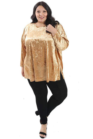 a dark haired woman wearing a gold crushed velvet swing top and back leggings