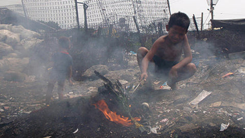 Filipino child burning cables for copper