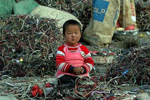 a Chinese child sitting among ewaste