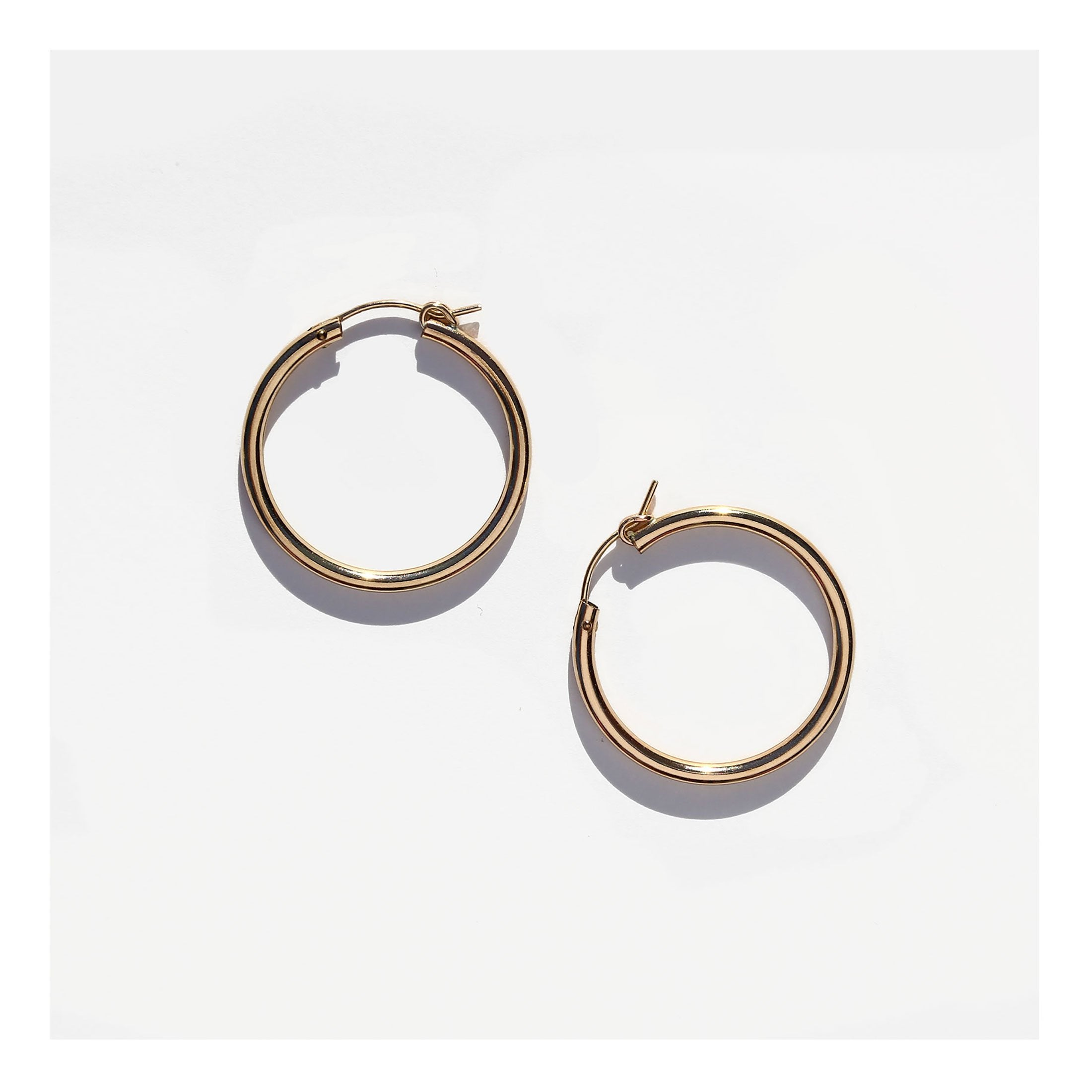 Thick gold hoop earrings in 14k gold filled metal, medium sized