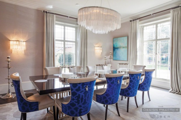 luxury dining space with bright blue chairs, chandelier and lacquered dining table - design practice by uber