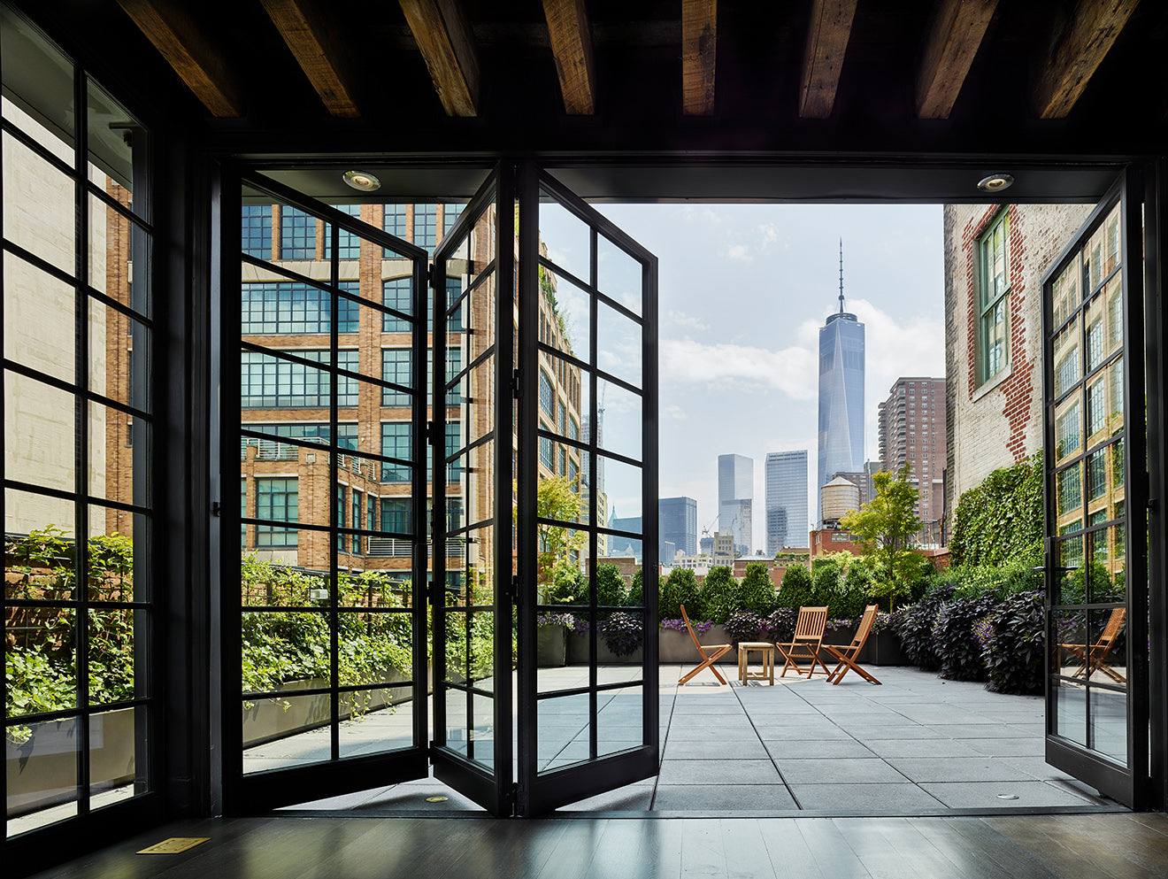 Industrial black windows and doors open up onto the terrace with views of the World Trade Center