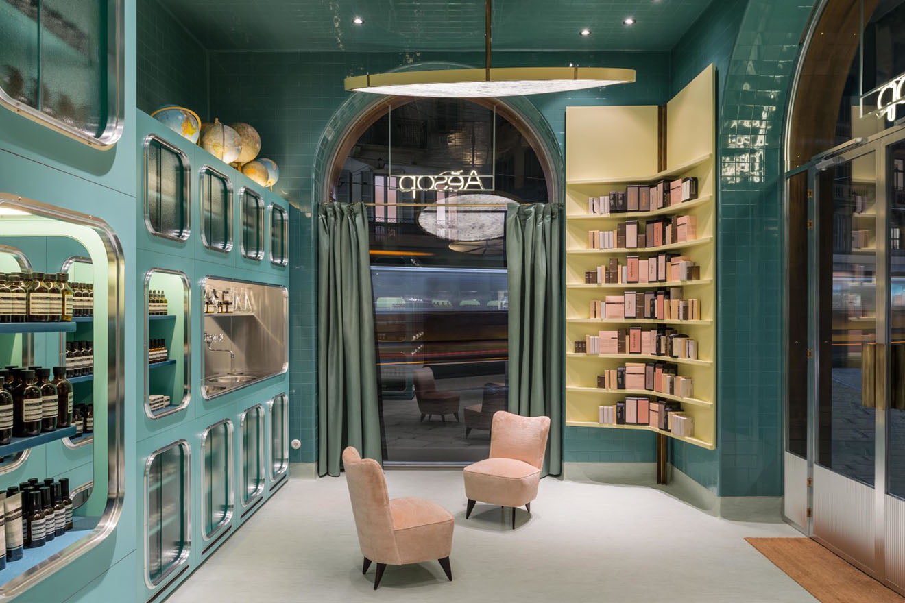 Aesop Store Milan with beautiful green tiles and decoration with pink upholstery