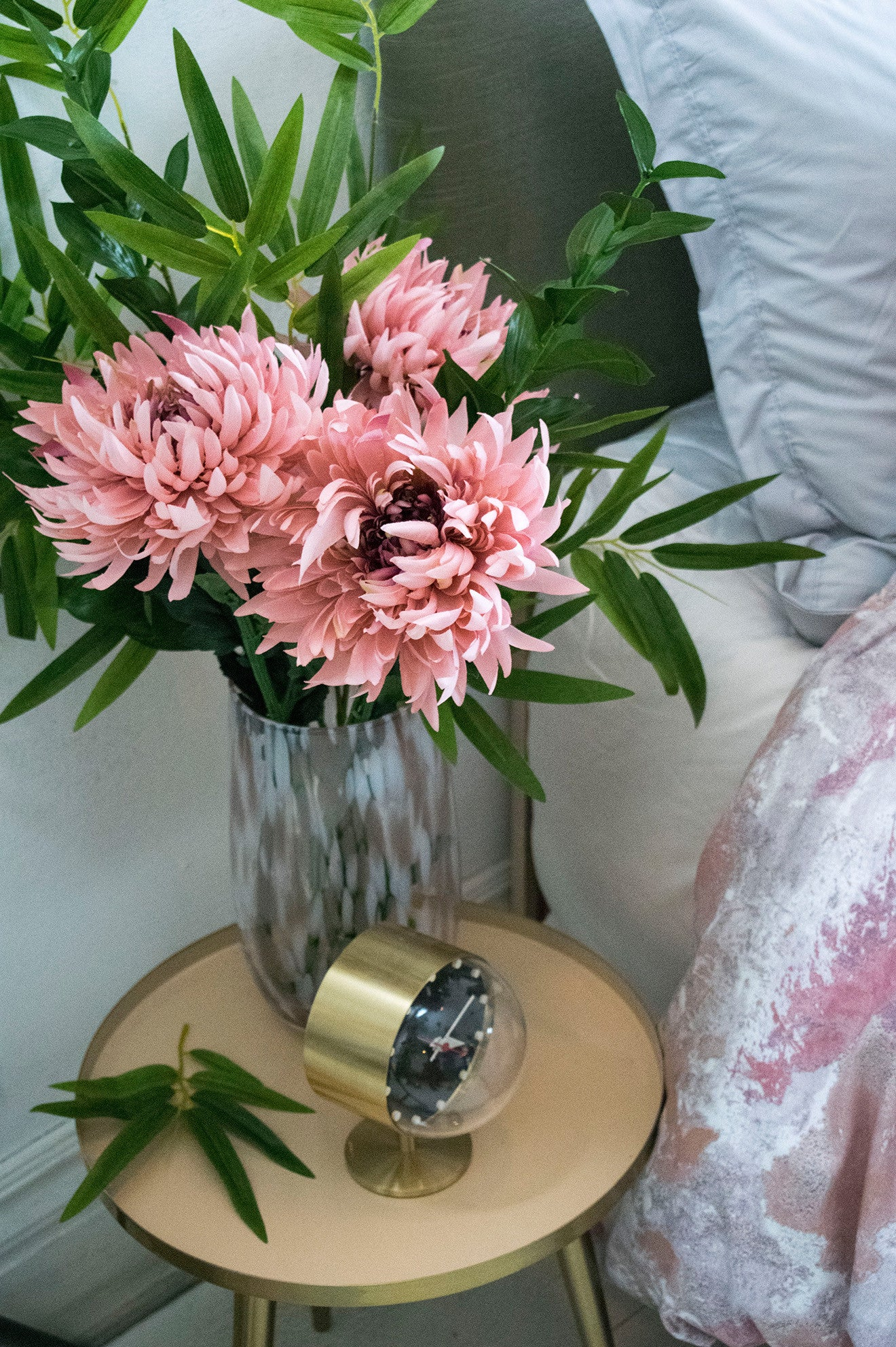 Brass bedside clock with floral and pastel bedding by Amara