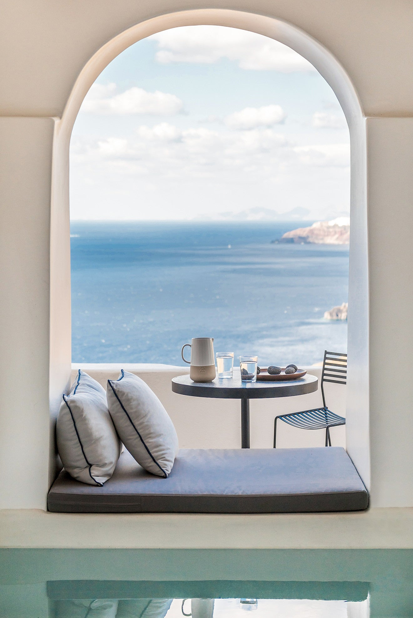 seating within the archway window, looking out across the sea - Laboratorium designs the beautiful Porto Fira Suites in Santorini