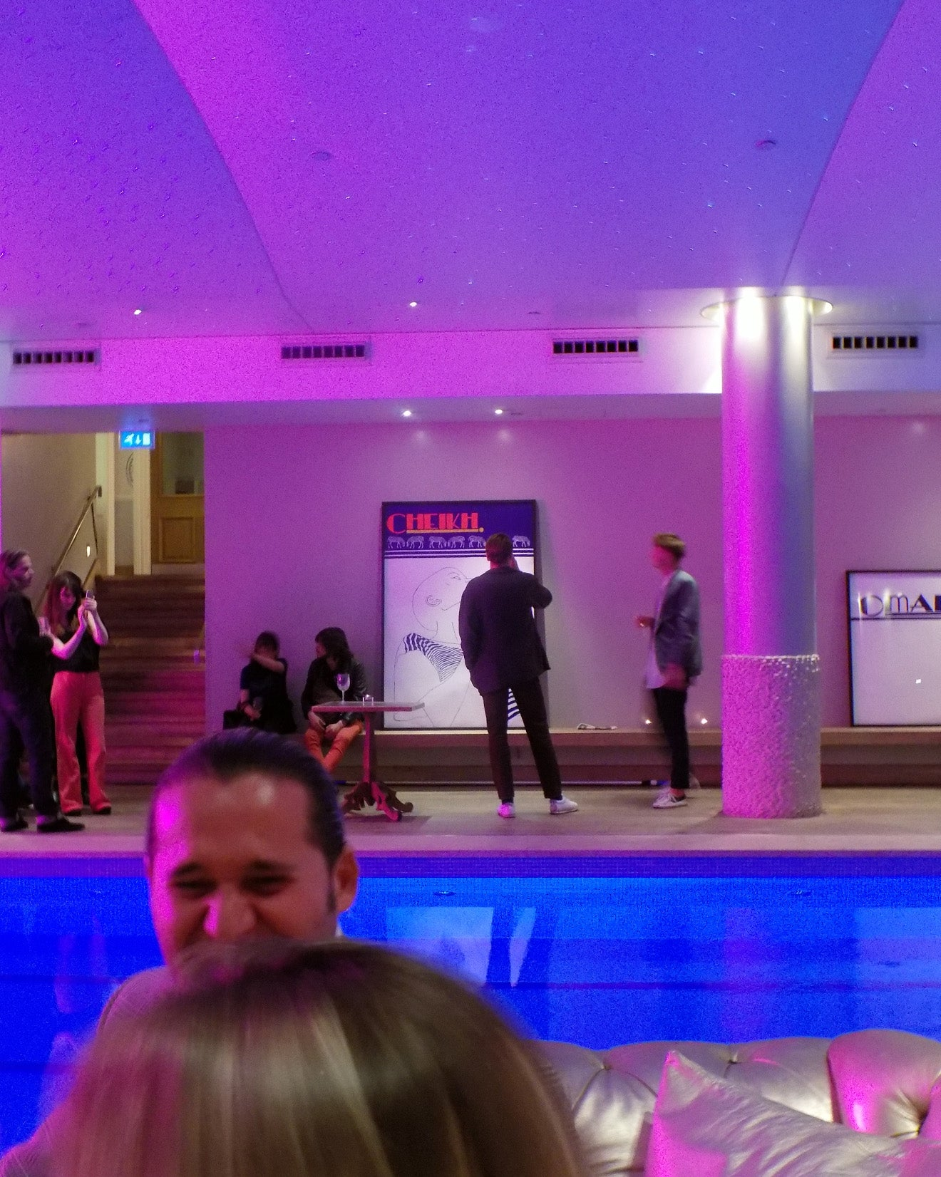 people viewing art designs by the pool at the Haymarket Hotel London