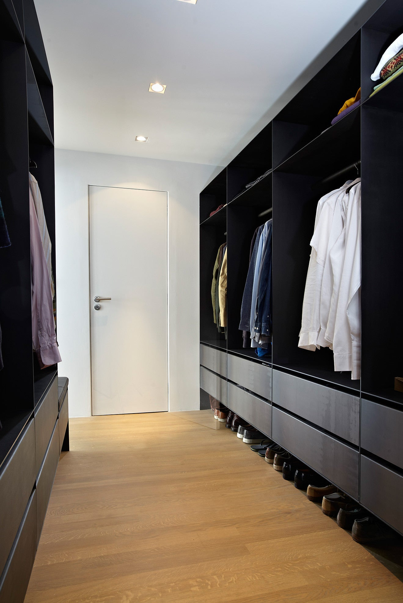 simple walk in wardrobe with natural wood floor and black lacquered wood finished wardrobes